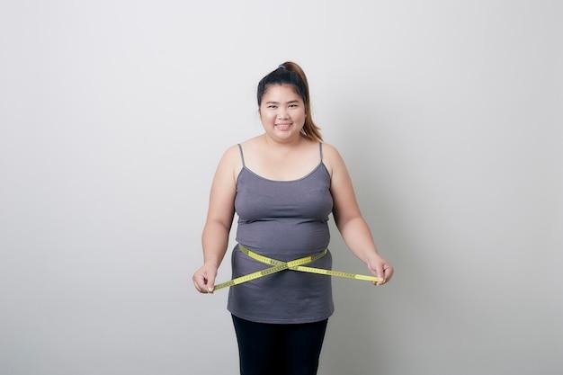 太りすぎの女性が彼女の脂肪腹を測定