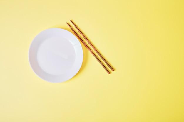 Пустая белая тарелка с деревянными палочками на желтом