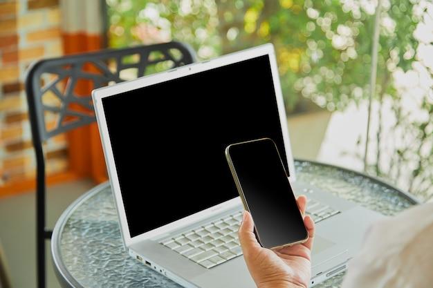 Женщина, используя мобильный смартфон и ноутбук