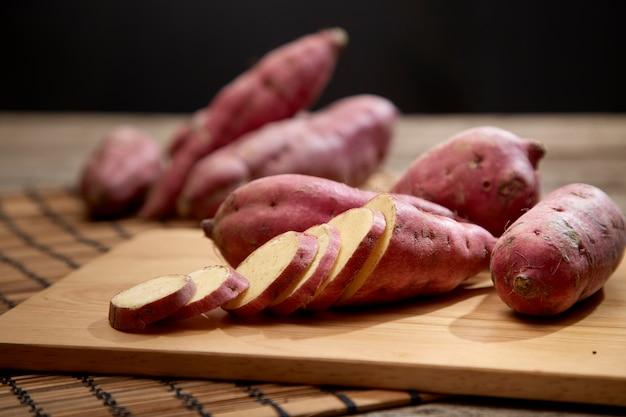 木製のテーブルに生のサツマイモ