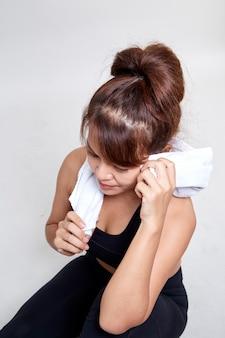Тренировка азиатская женщина питьевой воды, холдинг белое полотенце вокруг ее шеи