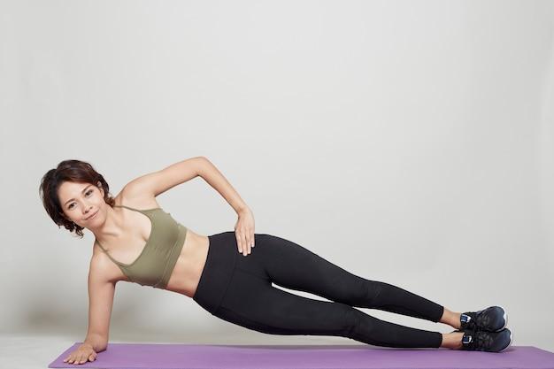 スタジオグレーの背景にアジアの女性によるストレッチトレーニング姿勢