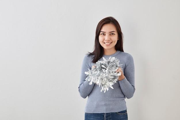 Женщина, держащая рождественскую серебряную мишуру