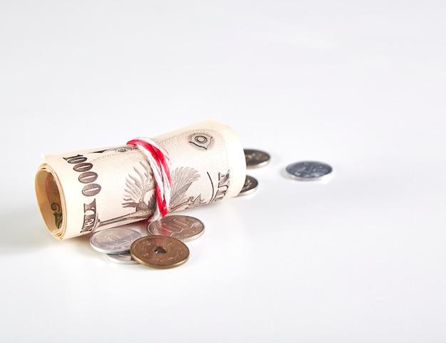 Банкноты японской иены и монеты японской иены на белом фоне