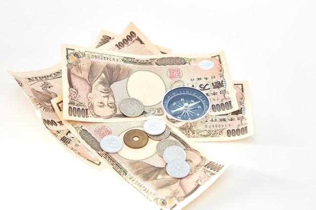 白い背景に日本の円の紙幣と円のコインとコンパス
