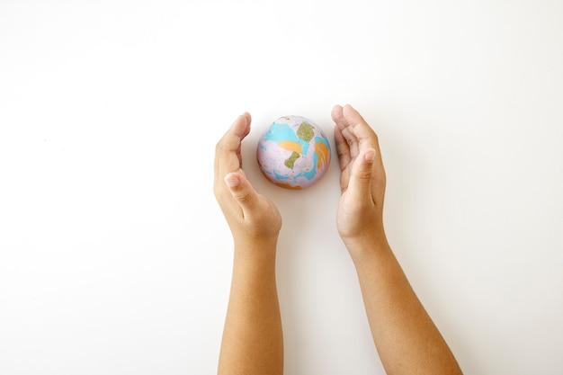 手は地球地球のプラスチリンのシンボルを保持します。