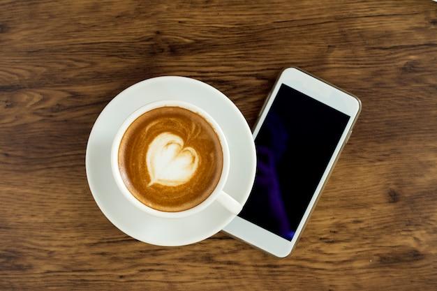 木製の背景にカフェラテアートコーヒーとスマートフォン