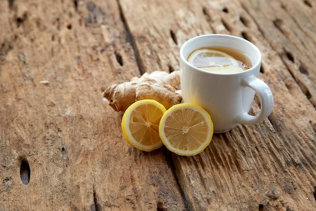 木製のレモンとジンジャーティーのカップ