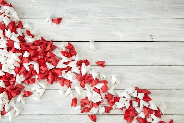 Белое и красное бумажное сердце на деревянном