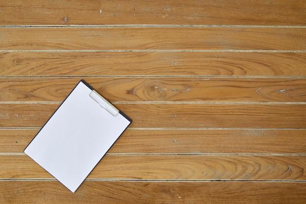 木製の背景に白いシートとクリップボード