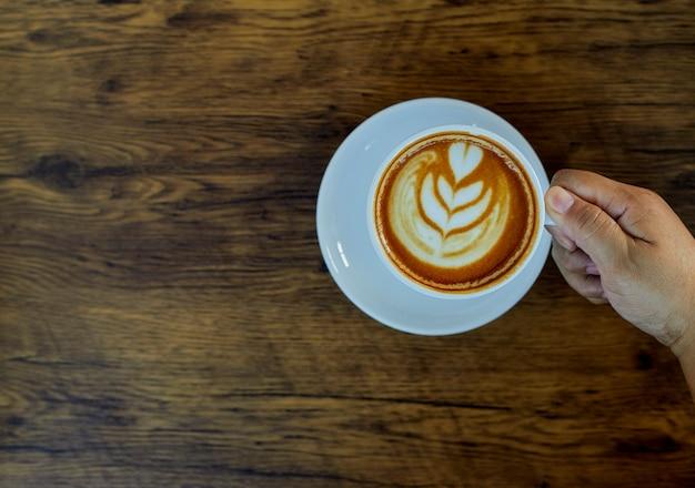 Рука держит чашку кофе на столе