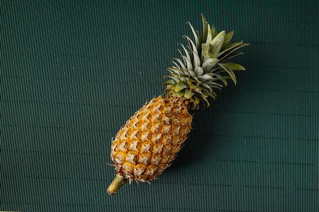 緑の紙の背景にパイナップル