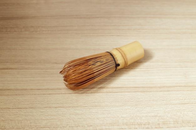 木製のテーブルに抹茶の竹茶泡立て器