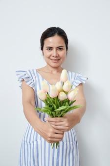 美しい女性のチューリップの花束を保持