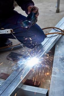 溶接工は工場で鋼を溶接している