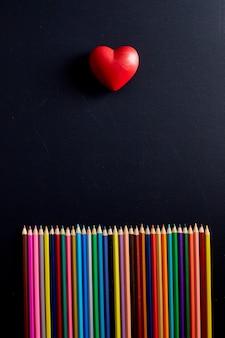 ハート形の色鉛筆学校に戻るコンセプトバナー黒板