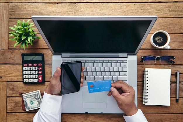 Человек держа кредитную карточку и используя портативный компьютер.
