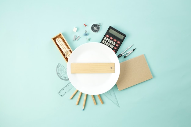 Школьные принадлежности вокруг пустой белой тарелки