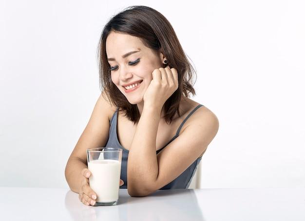 テーブルの上に牛乳を飲む若い女性