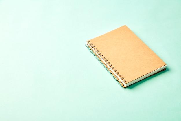 パステル調のオフィスの机の上に鉛筆とノート