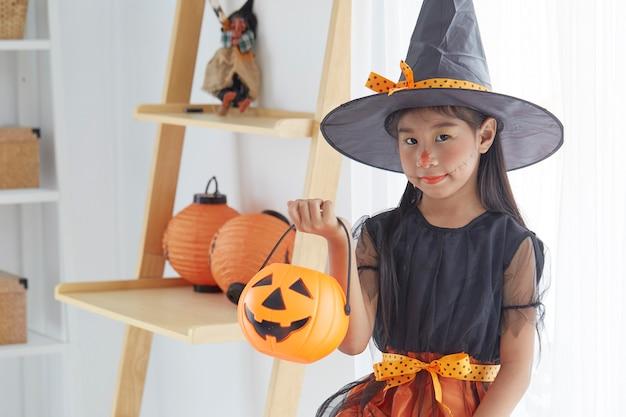 ハロウィーンの魔女の衣装で幸せな子供の女の子