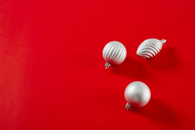 赤の背景に銀のクリスマスボールを置く