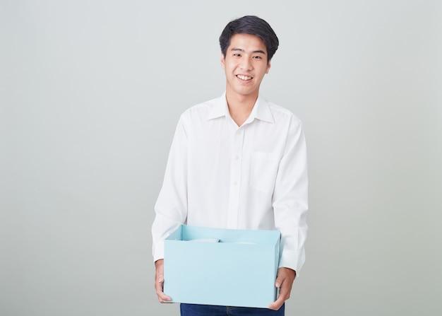 Молодой азиатский бизнесмен держа коробку