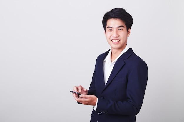 スマートフォンを使用して若いアジア系のビジネスマン