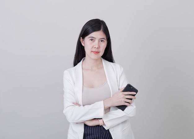 黒の携帯電話を保持している若いアジア女性
