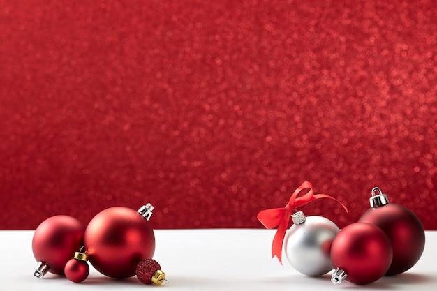 Рождественские шары на белом столе красная стена