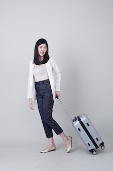 Молодой азиатский турист женщины с багажом для того чтобы путешествовать