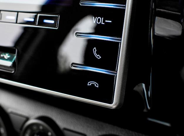 Кнопки управления телефоном на мультимедийной панели управления в роскошном автомобиле.