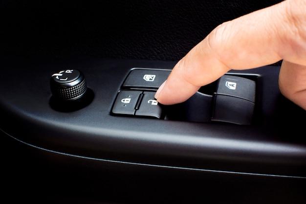 車のドアのロックボタンを指で押して、車のドアをロックおよびロック解除します。
