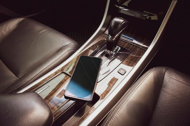 Смартфон размещают на автомобильной консоли в роскошном автомобиле.