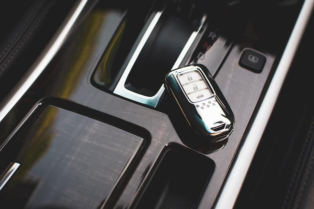 Пульт без ключа автомобиля хромированного цвета размещен на автомобильной консоли класса люкс.