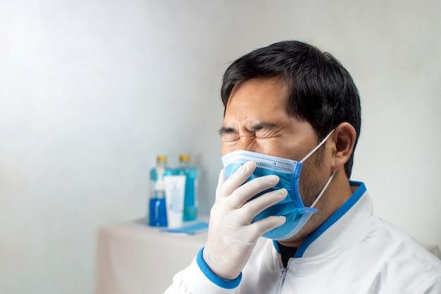 病院の白い部屋で医療用マスクで咳をする医師。