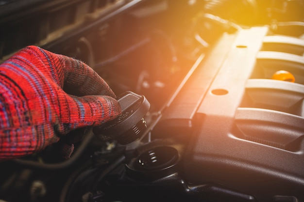 Рука механика раскрывает крышку масла двигателя автомобиля для обслуживания в гараже ремонта автомобиля.