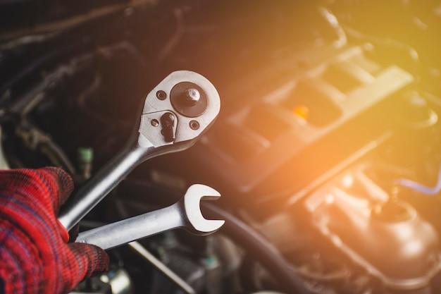メカニックのプロの男の手が車の修理ガレージ、自動車整備コンセプトで背景をぼかした写真を車のエンジンとレンチツールを保持します。