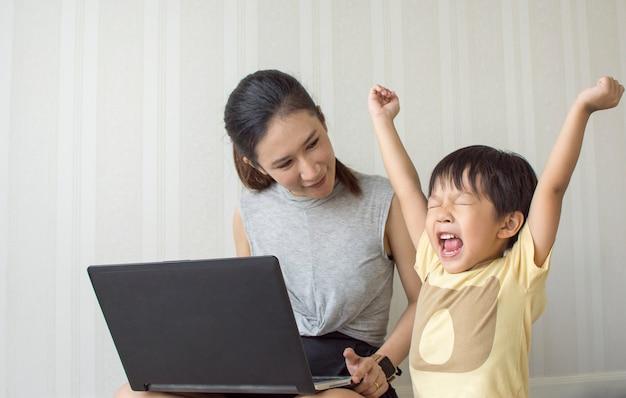 Мама и маленький сын аплодисменты во время игры на ноутбуке