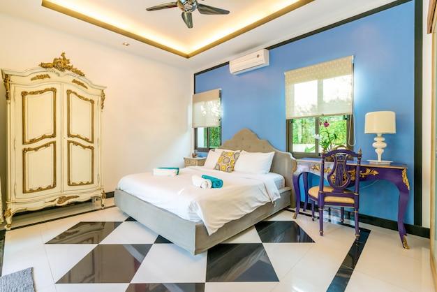Роскошный дизайн интерьера в спальне виллы с бассейном с уютной двуспальной кроватью