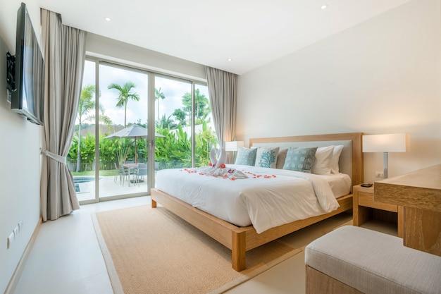 家や家の中でベッドの上の高い上げられた天井とバラとプールヴィラの寝室の豪華なインテリアデザイン