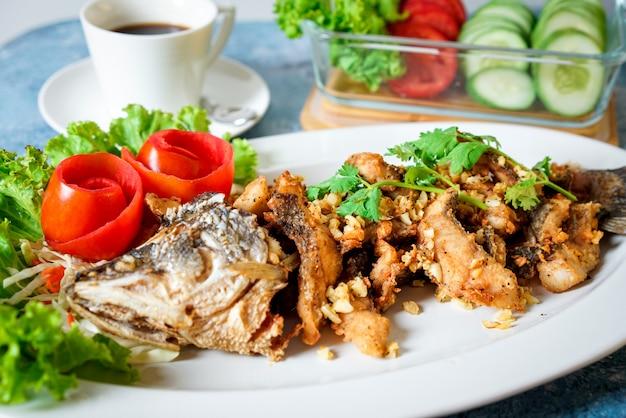 白いコーヒーカップと野菜の青いテーブルの上のニンニクと魚のフライ