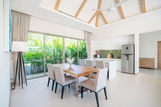 プールヴィラのリビングルームの豪華なインテリアデザイン。オープンキッチンのある高い天井の開放感のある明るく開放的な空間