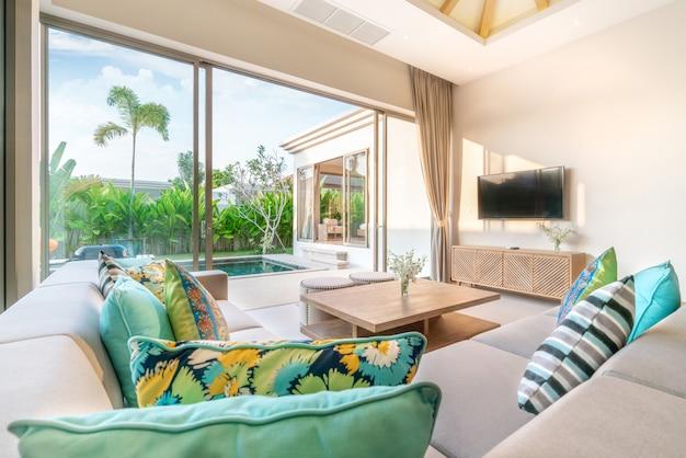 Роскошный дизайн интерьера в гостиной виллы с бассейном. просторное и светлое пространство с высоким поднятым потолком, диваном, средним столом, столовой