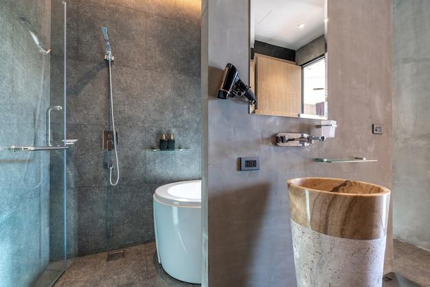 バスタブと洗面台付きの明るいデザインのインテリアデザインのバスルーム