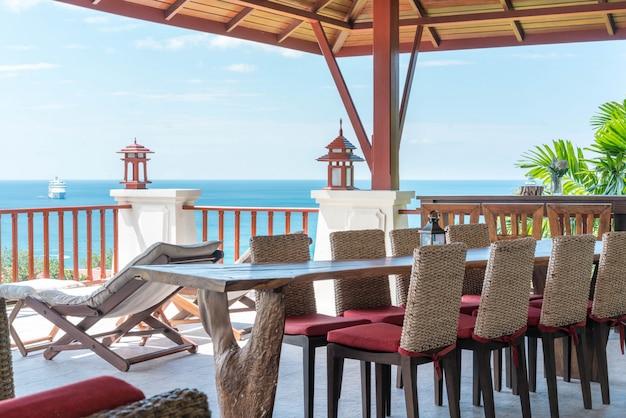 太陽のベッドとダイニングテーブルの家の海の景色のバルコニー