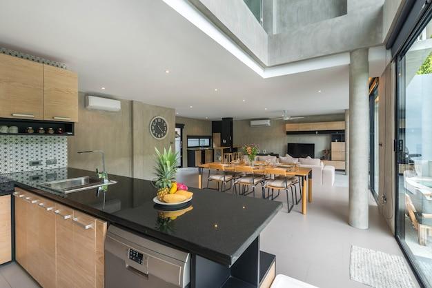島のカウンターとダイニングテーブルが備わるキッチンエリアの贅沢なインテリアデザインのロフトスタイル