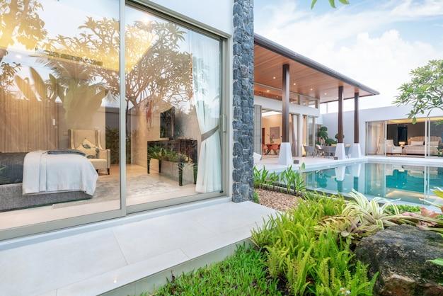 緑豊かな庭園と寝室のあるトロピカルプールヴィラを示す家または家の外観デザイン