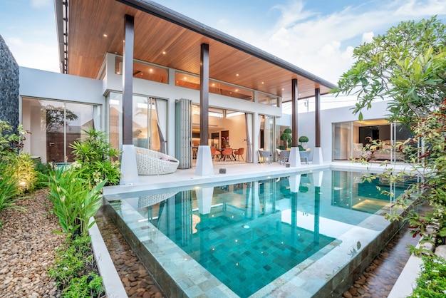 家や家を建てる緑豊かな庭園と寝室のあるトロピカルプールヴィラを示す外観とインテリアのデザイン