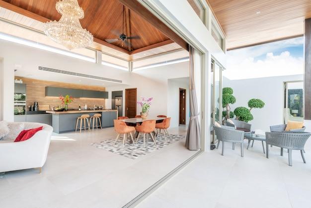 Дизайн интерьера в гостиной и открытой кухне с обеденным столом